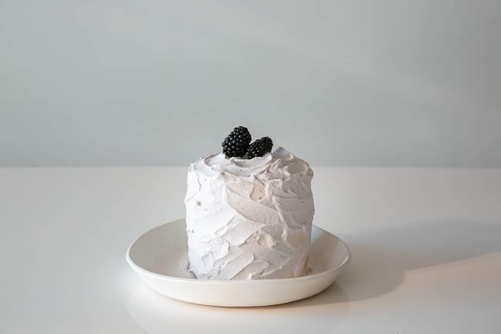 a white smash cake for a baby with blackberries on top