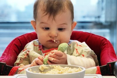 a baby looking at a spoon with a EZPZ suction bowl/plate in front of her