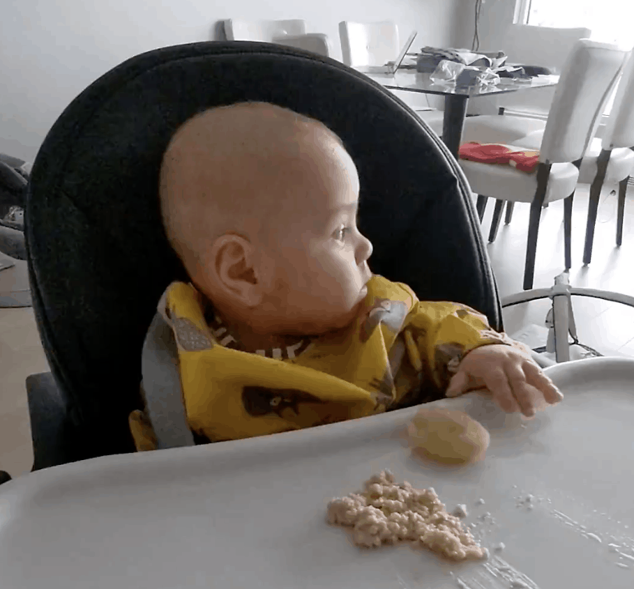 a baby in a high chair looks away from his food, uninterested in eating