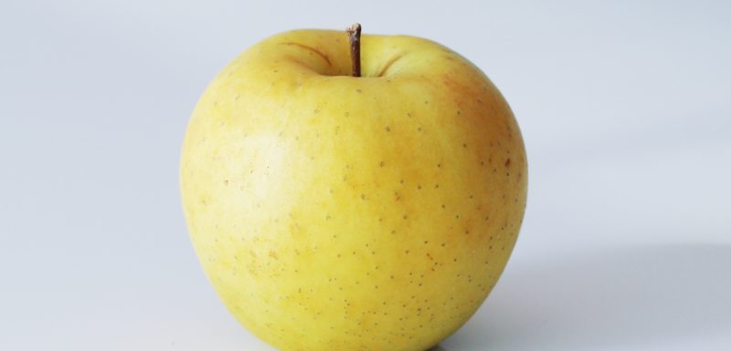 a golden delicious apple on a table before being prepared for babies starting solid food