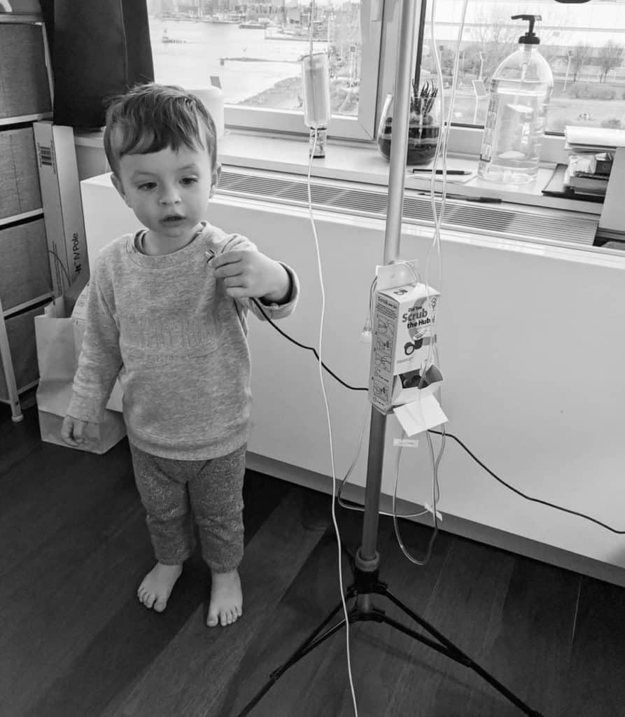 Atlas, 2 years, holds his mother's IV line in the hospital