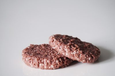 two beyond meat burger patties on a white table before being prepared for babies starting solid food