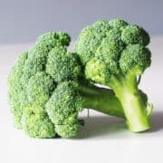 two heads of broccoli on a table before being steamed for babies starting solids