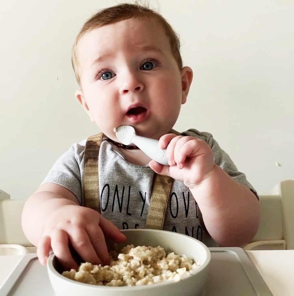 Baby Levi holds a spoon and grabs at some oatmeal