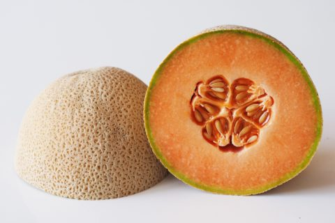 a cantaloupe cut in half before being prepared for babies starting solids