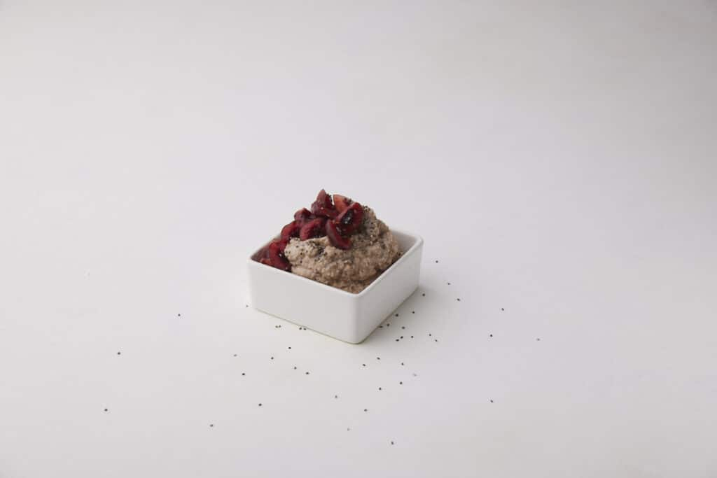 a square container of buckwheat porridge with quartered cherries on top