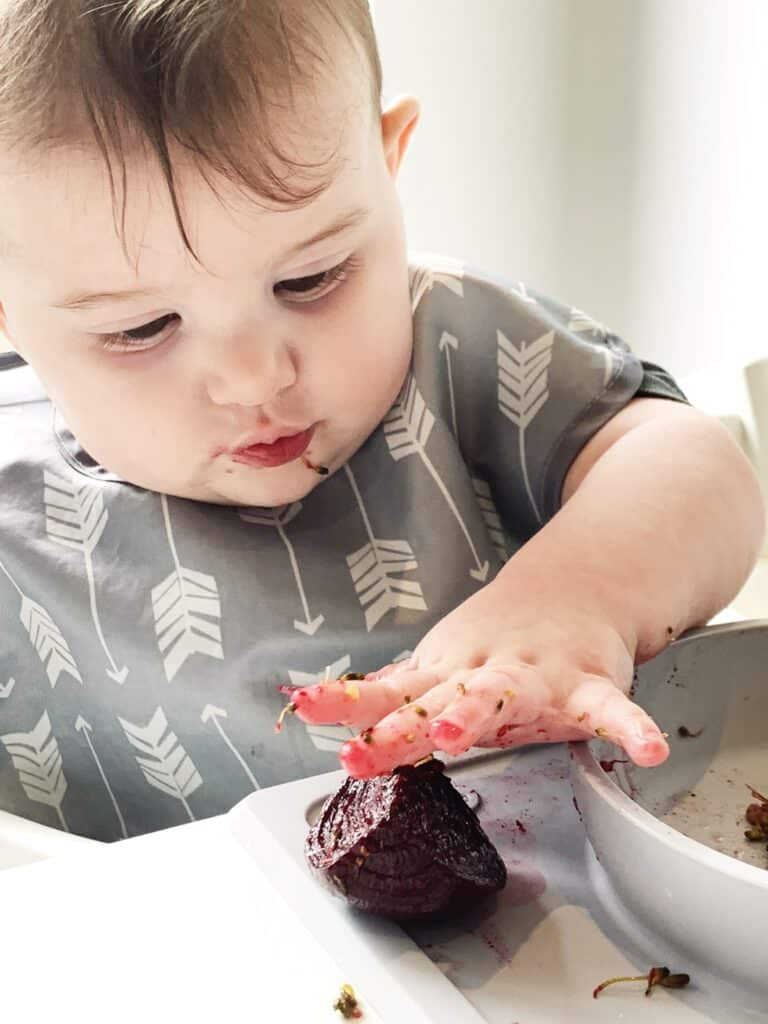 a baby reaches for a beet