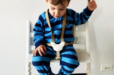a toddler boy looks down at his footrest from a Stokke Tripp Trapp chair