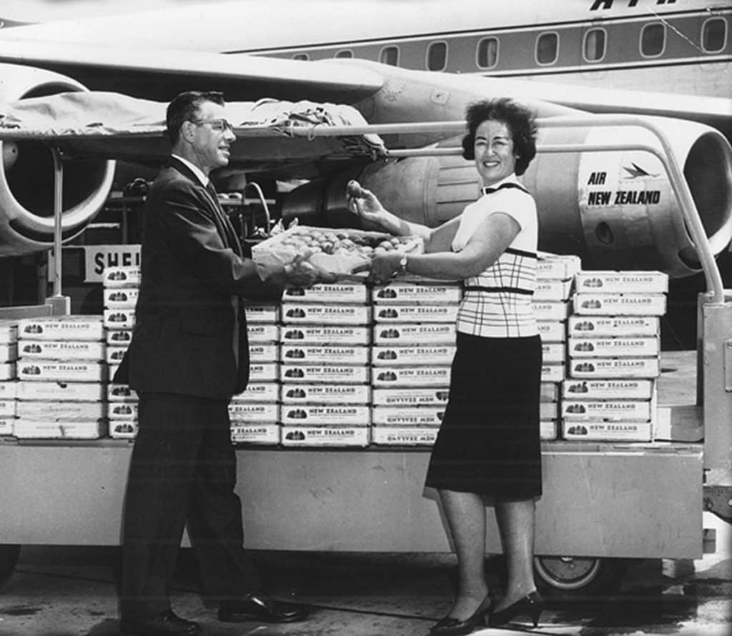 Frieda Caplan in front of an airplane delivering kiwifruit to the U.S.