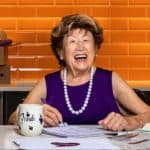 Frieda Caplan at a desk in a purple dress with pearls