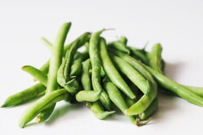 a pile of fresh green beans on a table before being prepared for babies starting solids