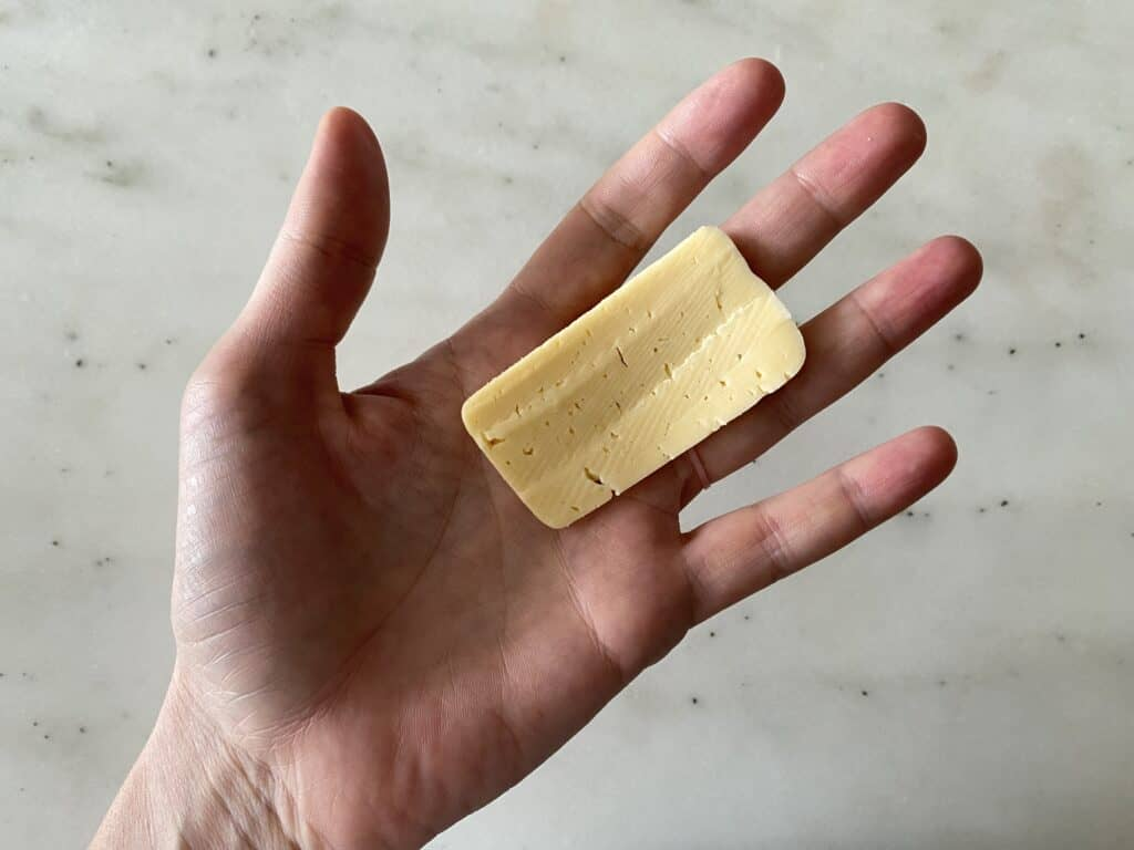 Ruler thin slice of Havarti cheese for babies on an adult hand
