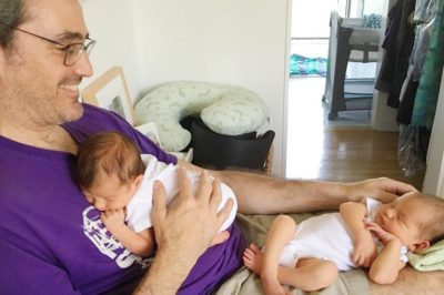 a father holds his twin babies on his lap