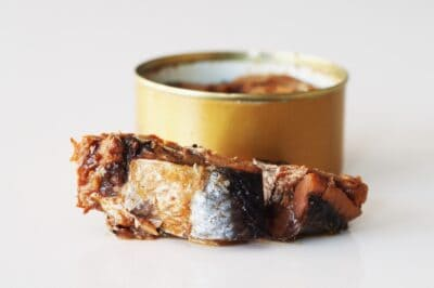 A gold can of herring with no label and a herring filet in front of it before being prepared for babies starting solids