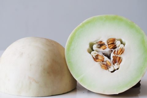 a whole honeydew melon cut in half before being prepared for babies starting solid food