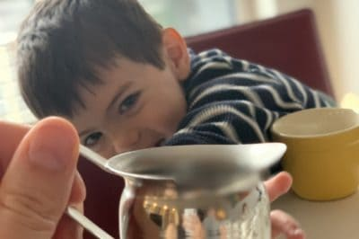 a four year old boy reaches for a sliver cream pitcher