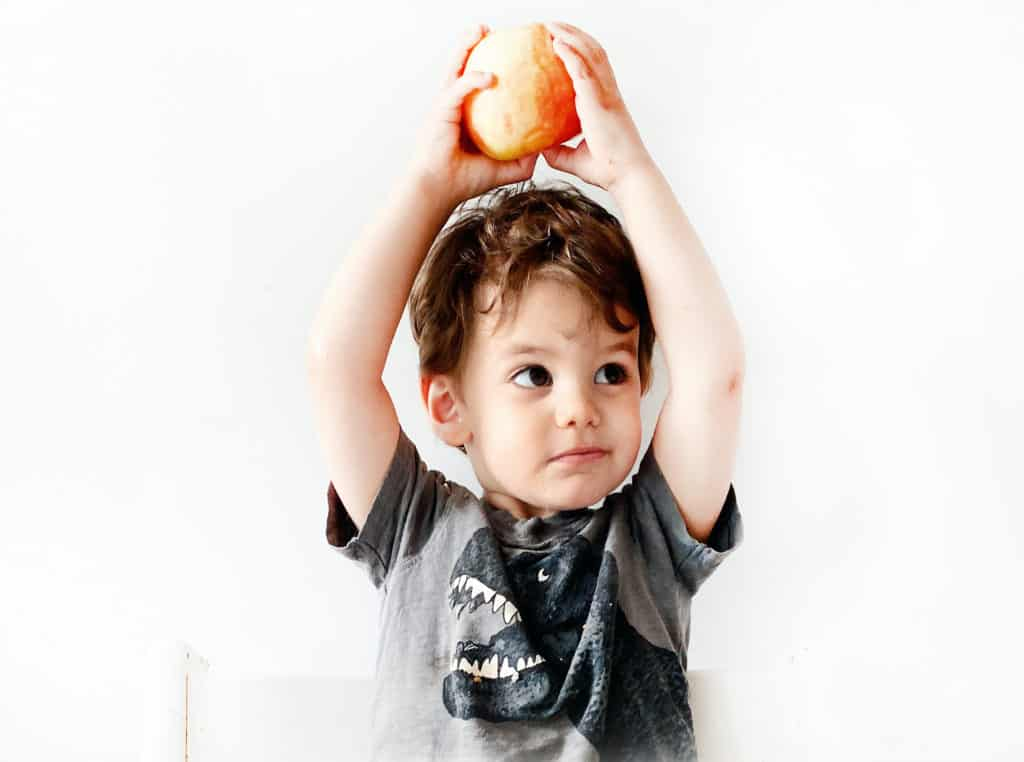 a toddler holding an apple over his head