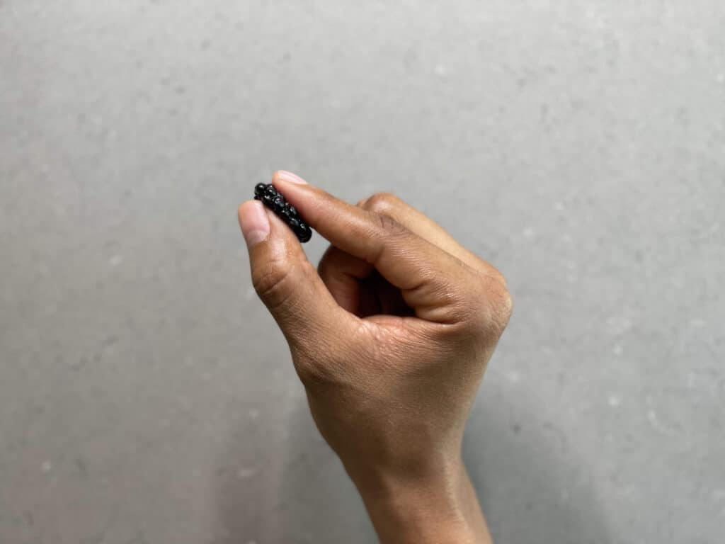 a hand holding a blackberry pressed between thumb and forefinger for babies 6 months+