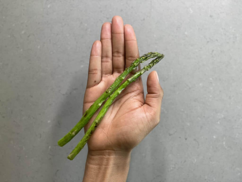 a hand holding 2 whole cooked asparagus spears for babies 6 months+