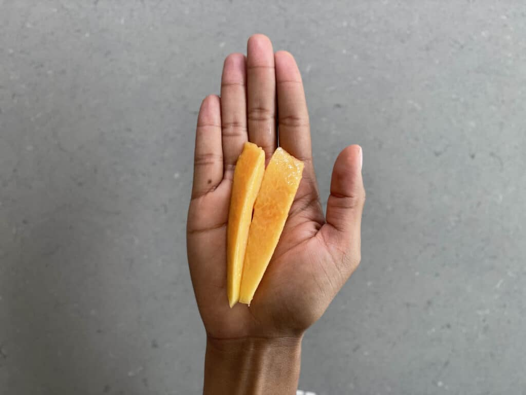 a hand holding two thin handles of soft, ripe papaya for babies 6 months+