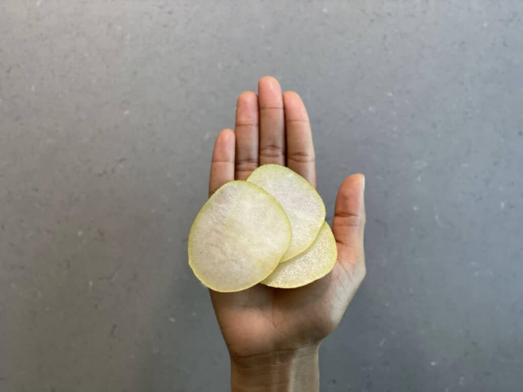a hand holding paper-thin rounds of Asian pear for babies 9 months+