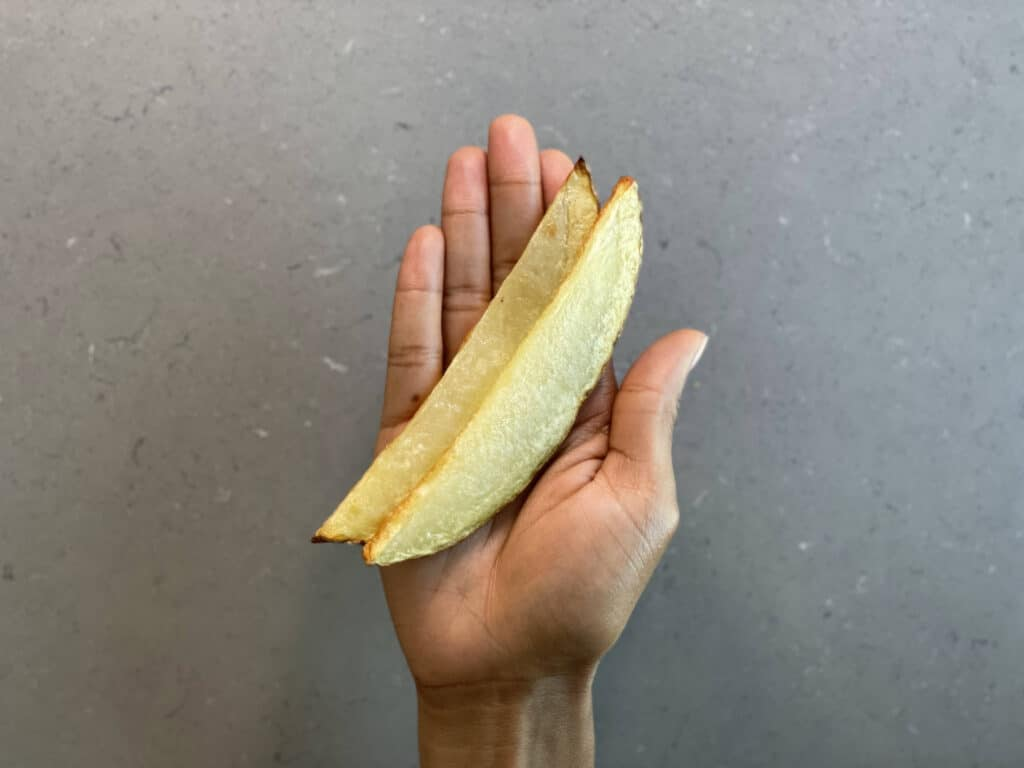 a hand holding two long cooked spears of potato for babies 6 months+