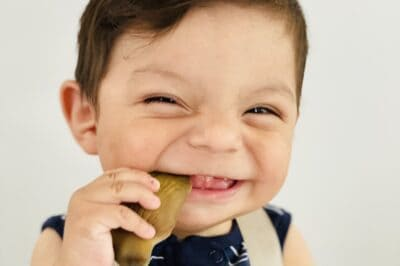 a smiling baby with dark hair holding a piece of artichoke in the side of his mouth