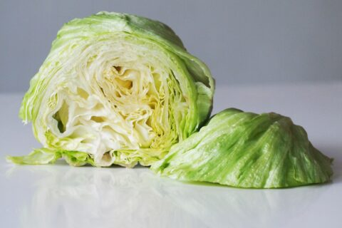 a head of iceberg lettuce cut in half and before being shredded for babies starting solids