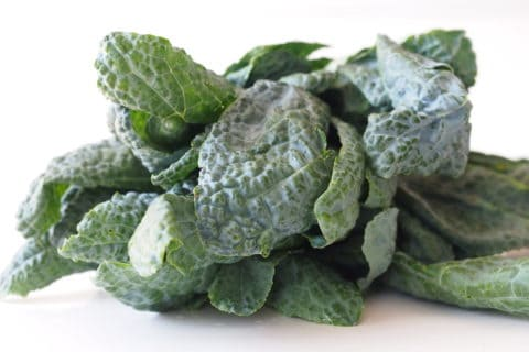 a pile of raw lacinato kale on a white table before being prepared for babies starting solid food