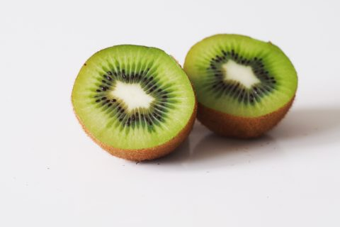 A kiwi cut in half on a table before being prepared for babies starting solid food
