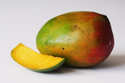 a mango with a piece cut away on a table before being prepared for babies starting solid food
