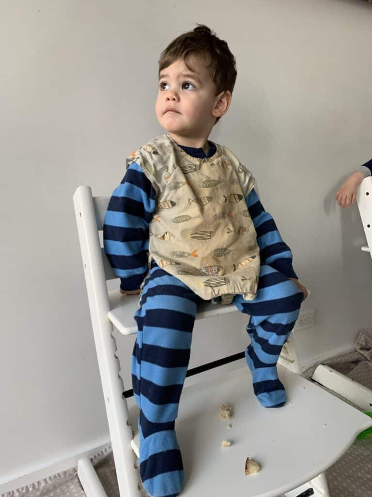 baby in footed pajamas and a bib sitting in a highchair