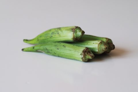 3 okra pods on a table before being prepared for babies starting solid food