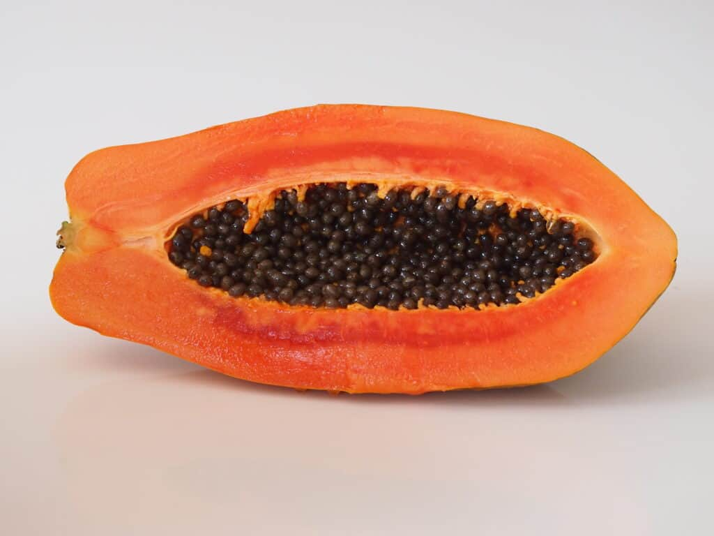 a papaya cut in half before being prepared for babies starting solids