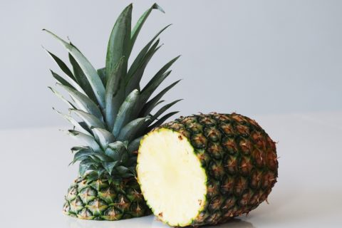 A whole pineapple with the crown cut off and standing next to it before being prepared for babies starting solid food