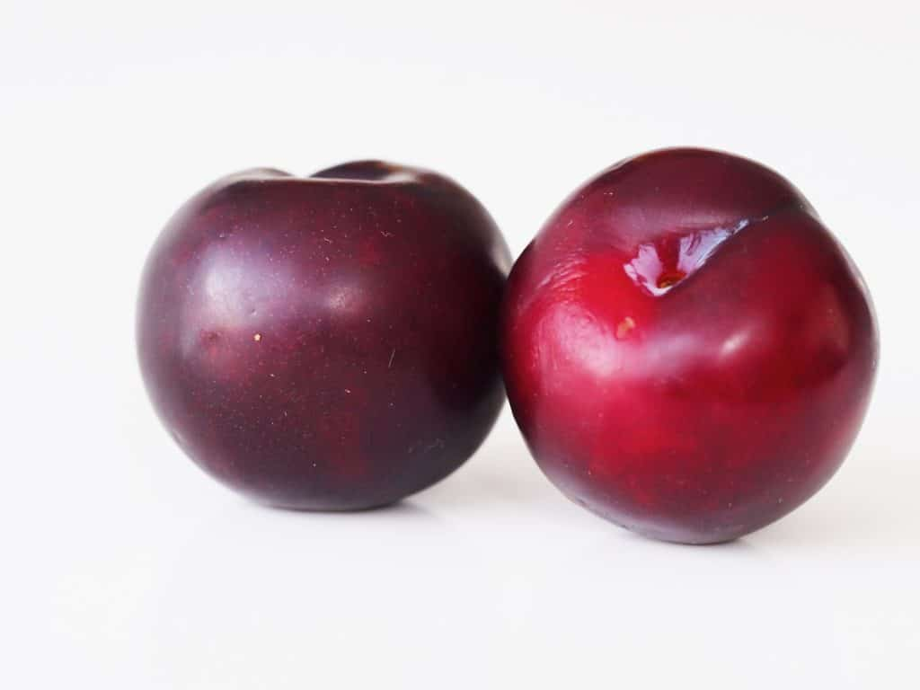 Two whole raw plums before they have been prepared for a baby starting solid foods