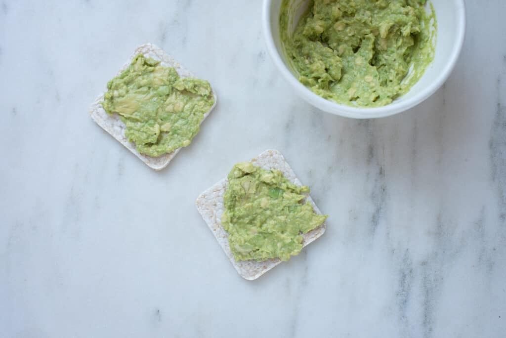 bowl of guacamole with 2 guacamole-topped crackers on the side