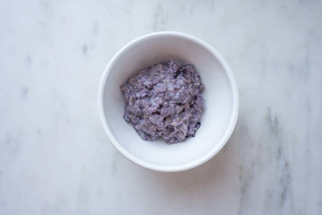 bowl of purple oatmeal (oats with mashed blueberries)