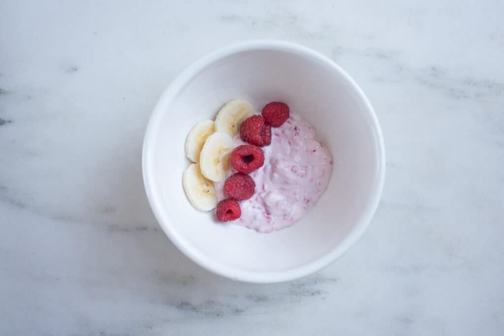 bowl of smashed raspberries with Greek yogurt, topped with whole raspberries and banana slices
