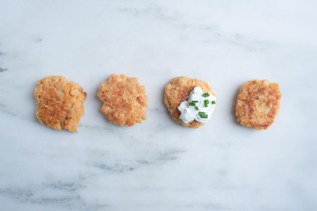 four salmon cakes, one of which is topped with mayonnaise