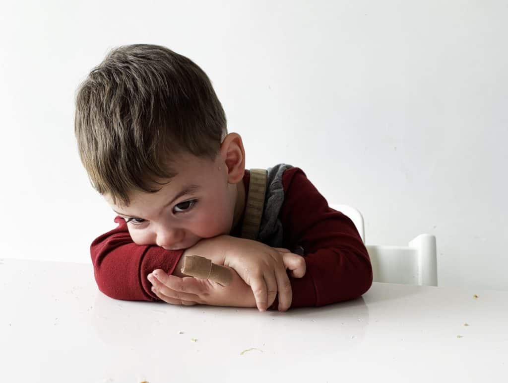 A toddler puts his head down on a table at a meal