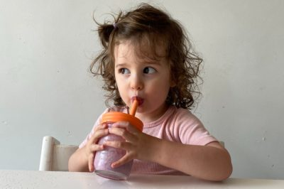 a toddler girl drinks a berry smoothie