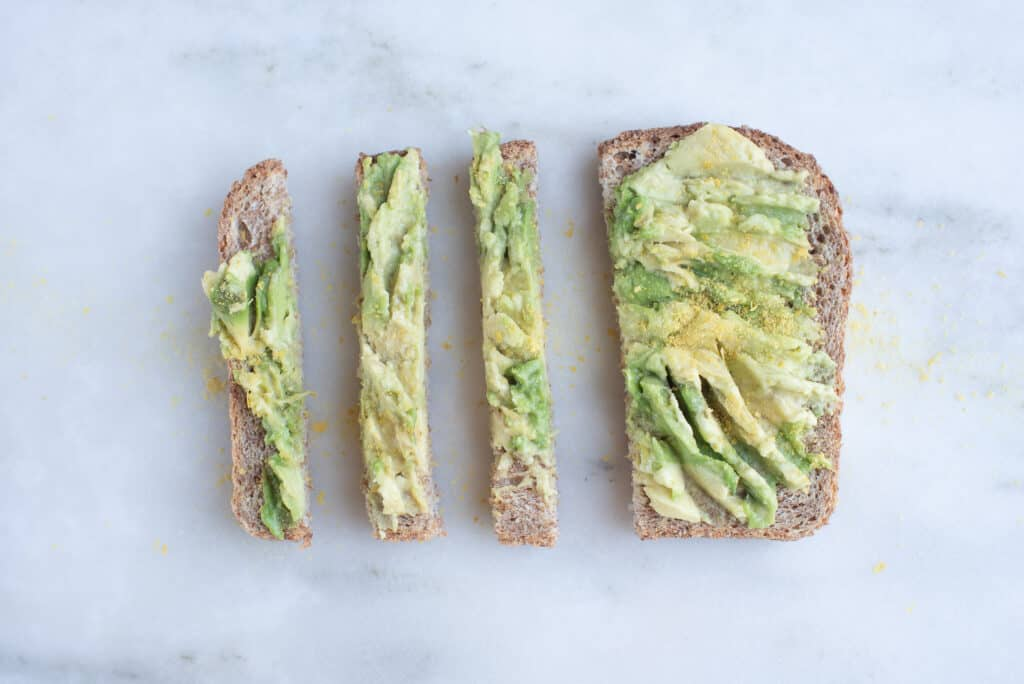 mashed avocado on toast slices, sprinkled with nutritional yeast