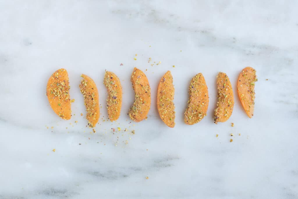 slices of apricot dusted with finely ground pistachios, sitting on a countertop