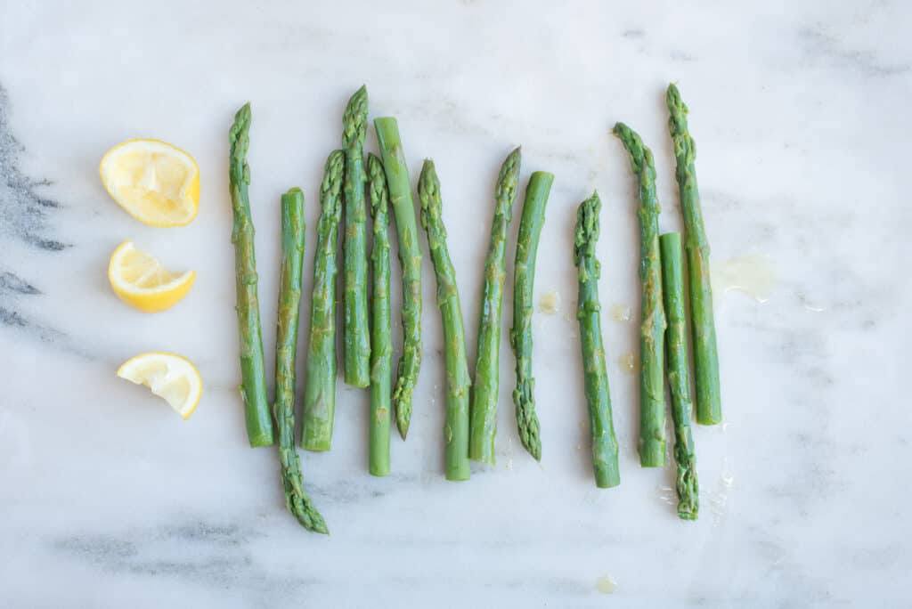 lemon wedges next to cooked whole asparagus spears on a white background