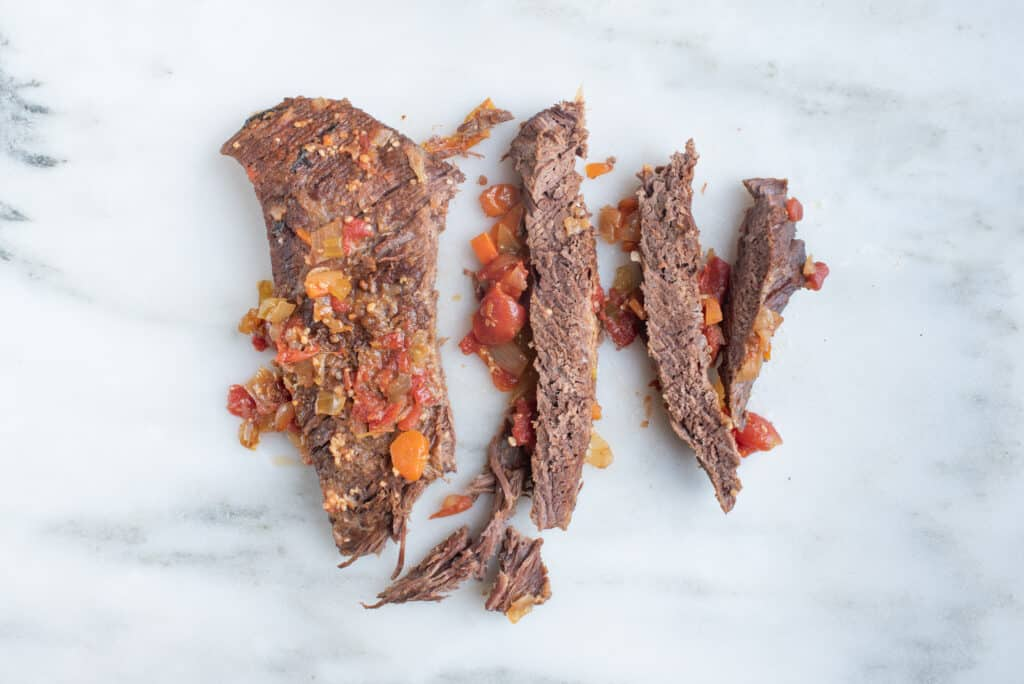 slices of braised beef brisket with chopped carrots and herbs, sitting on a countertop