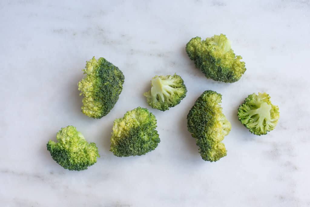 seven steamed broccoli florets sitting on a countertop