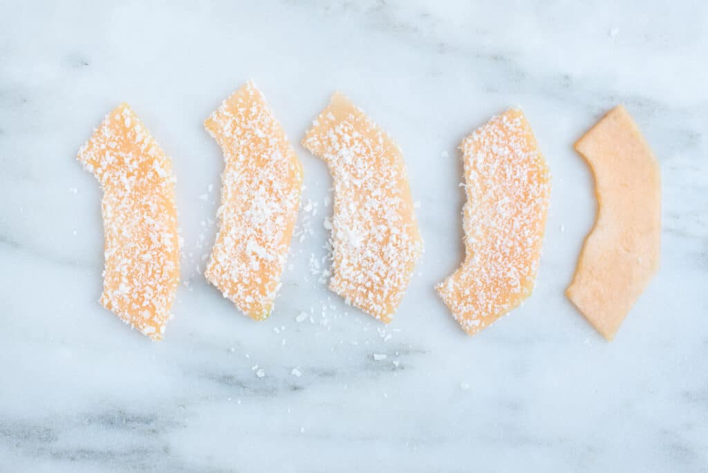 five wide, thin slices of cantaloupe dusted with finely shredded coconut