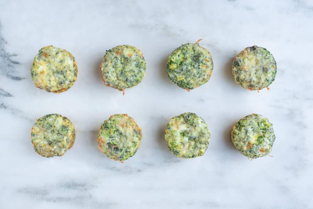 eight broccoli cheddar muffins sitting on a countertop