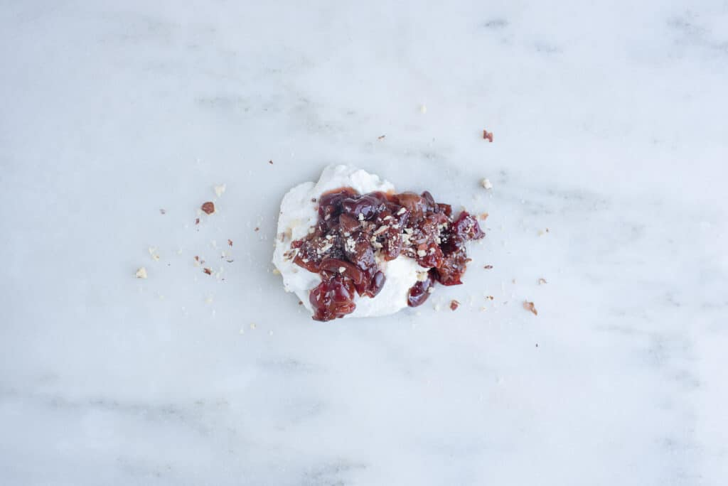 smashed cherries atop a pile of ricotta cheese on a counter
